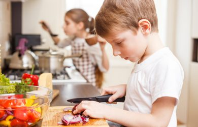 Small boy and his sister cooking in the kitchen. Little boy cutting onion for salad.
