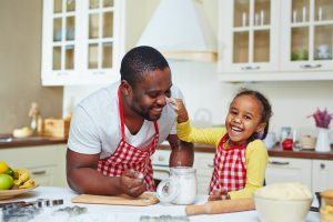 Joyful girl having fun with her father while cooking pastry